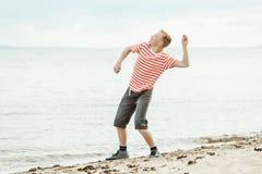 Piedras que lanzan del adolescente en el océano Foto de archivo libre de regalías
