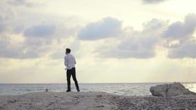 Piedras que lanzan del hombre feliz joven en el agua en la playa y el goce sorprendiendo la vista de la playa y del tiempo hermos metrajes