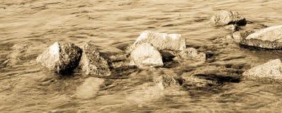 Piedras que miran fuera del agua Imagen de archivo libre de regalías