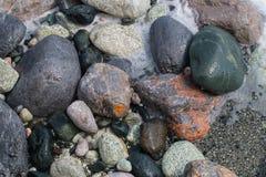 Piedras rayadas coloridas mojadas y redondeadas por las ondas Imagenes de archivo