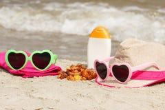 Piedras y accesorios ambarinos para las vacaciones el la arena en la playa, el concepto de protección del sol y el tiempo de vera Imagen de archivo libre de regalías
