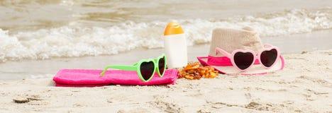 Piedras y accesorios ambarinos para las vacaciones en la arena en la playa, protección del sol, tiempo de verano Foto de archivo libre de regalías