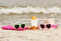 Piedras y accesorios ambarinos para las vacaciones en la arena en la playa, protección del sol, tiempo de verano Fotos de archivo libres de regalías