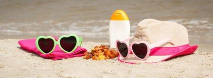 Piedras y accesorios ambarinos para las vacaciones en la arena en la playa, protección del sol, tiempo de verano Imagen de archivo libre de regalías