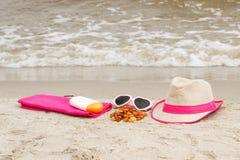 Piedras y accesorios ambarinos para las vacaciones en la arena, la protección del sol y el concepto del tiempo de verano Imagen de archivo libre de regalías