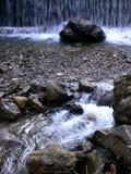 Piedras y canto rodado en el río delante de una cascada Fotos de archivo