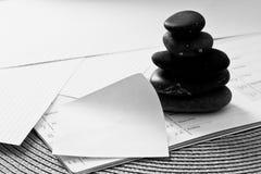 Piedras y nota vacía, metáfora del asunto para el balance Foto de archivo libre de regalías