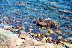 Piedras y ondas azules, mar tirreno, fondo Fotografía de archivo libre de regalías