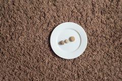 Piedras y placa en un fondo de la alfombra Foto de archivo libre de regalías