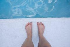 Pieds au bord de la piscine Photographie stock