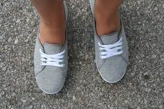 Pieds bronzés dans des chaussures grises d'été image libre de droits