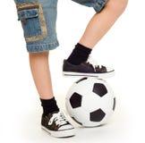 Pieds chaussés dans les espadrilles et le ballon de football Photographie stock libre de droits