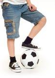 Pieds chaussés dans les espadrilles et le ballon de football Images stock