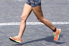 Pieds courant l'athlète de distance sur le trottoir en pierre Images stock