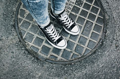 Pieds d'adolescent dans une paire de chaussures de toile noires Photo libre de droits