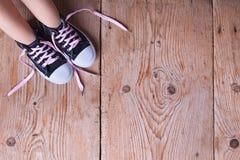 Pieds d'enfant dans des espadrilles sur le vieux plancher en bois Image libre de droits