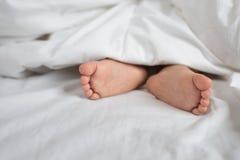 Pieds d'enfant en bas âge dans le lit, la feuille et l'oreiller blancs Photos stock