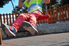 Pieds d'enfant sur l'oscillation au terrain de jeu Photos stock