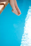 Pieds d'enfants contre la piscine bleue photo stock