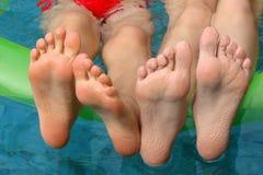 Pieds d'enfants dans une piscine Photographie stock libre de droits