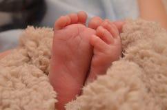 Pieds d'enfants en plan rapproché de lit Photographie stock libre de droits