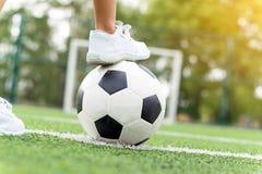 Pieds d'espadrilles blanches de port d'un garçon faisant un pas sur un ballon de football Photographie stock