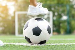 Pieds d'espadrilles blanches de port d'un garçon faisant un pas sur un ballon de football Photo stock