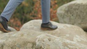 Pieds d'homme faisant un pas au-dessus des montagnes de rochers près de la colline de forêt d'une haute montagne clips vidéos