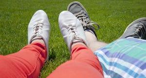 Pieds d'un couple se trouvant sur l'herbe Photographie stock