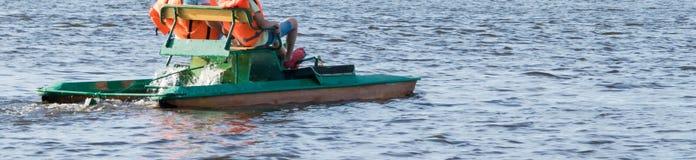 Pieds d'un enfant dans des pantoufles en caoutchouc pédalant un catamaran sur l'eau, longue photo photo libre de droits