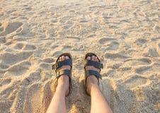 Pieds d'un homme détendant sur le sable Photographie stock