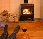 Pieds d'un homme simple détendant par le feu avec du vin Photo libre de droits