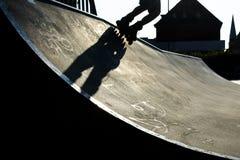 Pieds d'un rollerblader avec les patins intégrés montant au-dessus du halfpi Images stock