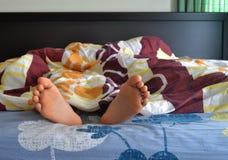 Pieds d'une femme dormant sur le lit Images libres de droits