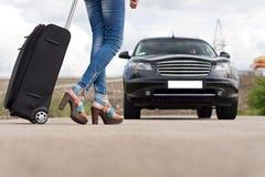Pieds d'une femme portant une valise noire de chariot Image stock