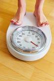 Pieds d'une femme sur l'échelle de salle de bains Image stock