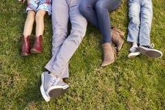 Pieds d'une jeune famille se trouvant sur l'herbe en parc, tir de culture Image libre de droits