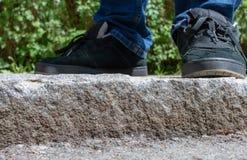 Pieds d'une personne se tenant sur des étapes en pierre extérieures Photographie stock