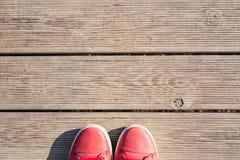 Pieds dans des chaussures roses occasionnelles sur le fond en bois de pilier Photos libres de droits