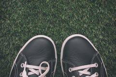 Pieds dans des chaussures sur l'herbe verte Images stock