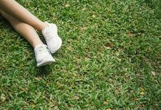 Pieds dans des espadrilles blanches dans l'herbe verte Photos libres de droits
