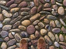 Pieds dans des espadrilles brunes sur le vieux trottoir en pierre médiéval Images libres de droits