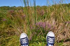 Pieds dans des espadrilles contre l'herbe Photo libre de droits