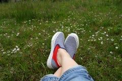 Pieds dans des espadrilles dans l'herbe verte Photo stock