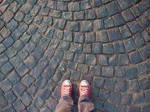 Pieds dans des espadrilles rouges sur la vue supérieure de trottoir, style informel Images stock