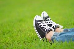 Pieds dans des espadrilles sur l'herbe verte Photographie stock libre de droits