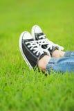 Pieds dans des espadrilles sur l'herbe verte Image libre de droits