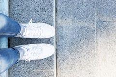 Pieds dans des espadrilles sur le fond de trottoir, vue supérieure Photographie stock libre de droits