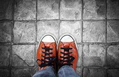 Pieds dans l'espadrille en cuir sur le fond de trottoir Photos libres de droits