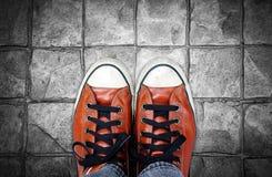 Pieds dans l'espadrille en cuir sur le fond de trottoir Image libre de droits